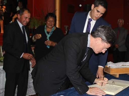 Back, Ian Perry (left), lead negotiator for Ngati Kahungunu ki Wairarapa Tamaki Nui a Rua in their Treaty of Waitangi settlement and Dannevirke's Maria Edwards look on as Lee Gray associate director, Deloitte Deloitte Touche Tohmatsu Limited, guides Chris Finlayson in the signing of the agreement in principle.
