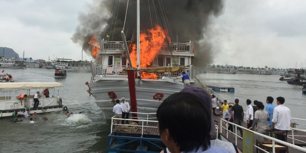 Loading Passengers jump from a cruise ship at Halong Bay. Which went up in flames. The woman sitting on the edge of the boat is believed to be a Kiwi. Photo / Andrew McVey