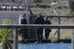 Police search an area and old derelict swimming pool behind the burnt out house at Hokio in April.