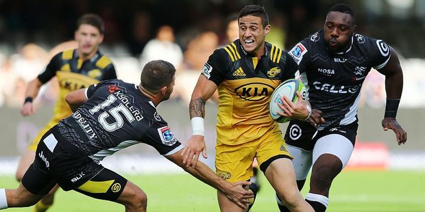 Sharks fullback Willie le Roux attemps to bring down Hurricanes halfback TJ Perenara. Photo / Getty