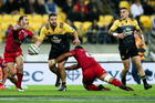 Dane Coles of the Hurricanes looks to pass in the tackle of Hendrik Tui of the Reds. Photo / Getty
