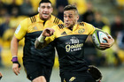 TJ Perenara of the Hurricanes looks to evade the challenge of Ayumu Goromaru. Photo / Getty Images