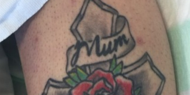 The woman has a tattoo of a cross with a rose, and has the words 'mum' and 'dad'. Photo / NZ Police