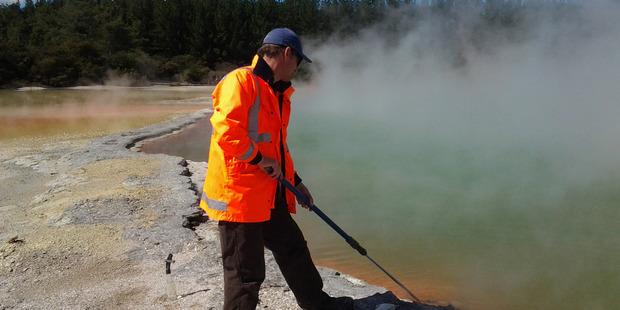 Matthew Stott takes samples from a geothermal area. Photo / Jean Power, GNS Science