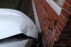 A white Nissan crashed into a house on Great North Rd in Waterview this morning. Photo / Jesse Bourke-Jackson
