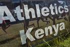 Junior athletes run past a sign for Athletics Kenya. Photo / AP