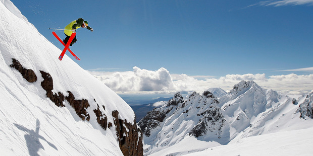 A skier flies off the bluff at Whakapapa, with the Pinnacles in the background. Photo / Sarah Ivey