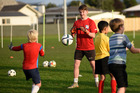 Ben Whitaker helps at a coach session for 50 young goalkeepers run by James Bannatyne. Photo/George Novak