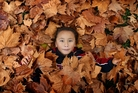 SEASONAL: Leanne Tauia, 6, covered in autumn leaves.PHOTO/JOHN BORREN