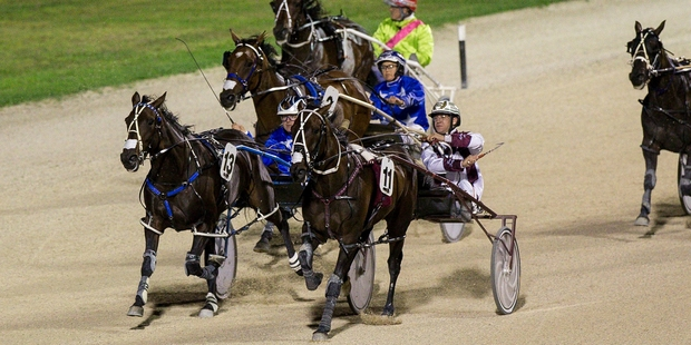 Dexter Dunn drives Christen Me (outer) to victory in the Auckland Cup last year. Photo / Dean Purcell