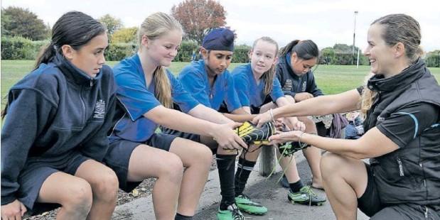 NEW KICKS: Football players Phoenicia Te Rito (left), Courtney Walker, Jaspreet Singh, Abby Scarborough and Jordan Purcell, of Heretaunga Intermediate, receive boots from Sport Hawke's Bay primary school development officer Sally McKenzie.
