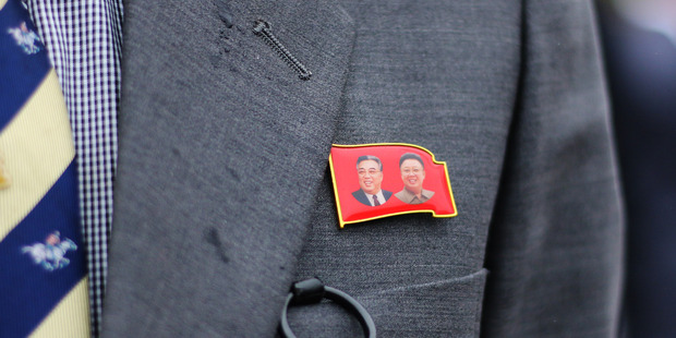 A man wears a pin featuring former North Korean leaders Kim Il Sung, left, and Kim Jong Il in Pyongyang, North Korea. Photo /  Bloomberg