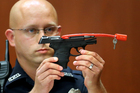 In this 2013, file photo, Sanford police officer Timothy Smith holds up the gun that was used to kill Trayvon Martin. Photo / AP