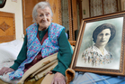 Emma Morano poses next to a picture depicting her when she was young, in Verbania, Italy. Photo / AP
