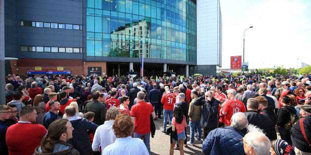Spectators stand outside of Old Trafford stadium after today's final soccer match of the season between Manchester United and AFC Bournemouth was abandoned. Photo / AP