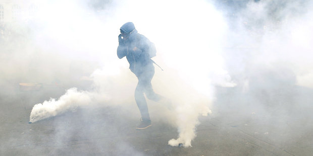 A demonstrator escapes through tear gas as he faces off with riot police officers during a protest in Paris today. Photo / AP
