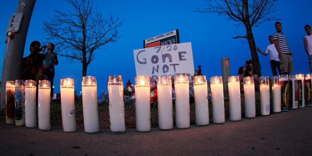 Candles sit illuminated along the pavement in front of a makeshift memorial for the victims of a mass shooting  in 2012 at the Aurora Mall in Aurora, Colorado. Photo / AP
