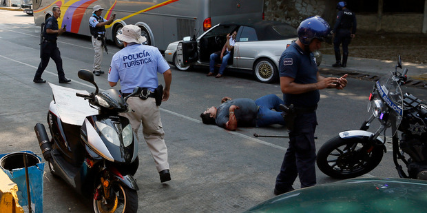 A wounded man lies on the ground and a second one sits in his car near Caleta beach in Acapulco, Mexico. Photo / AP