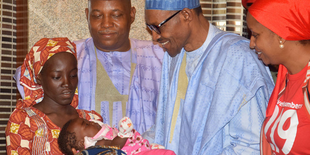 Amina Ali Nkeki (left) and her baby pose for photographs at the Presidential palace in Abuja with President Muhammadu Buhari (centre).  Picture / AP