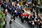 University of Auckland students walking up Queen Street on their way to their graduation ceremony. Photo / Martin Sykes