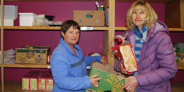 Co-ordinator and volunteer Lyn Tankersley and volunteer Krystal Logan prepare a food parcel from the increasingly bare shelves at the Masterton Foodbank. PHOTO/ALISA YONG