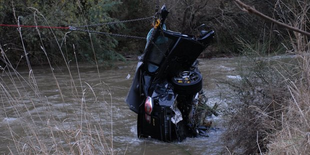 The wreckage of a late model Holden Comodore GTS is winched by heavy crane from the middle of the swollen Waipoua River.