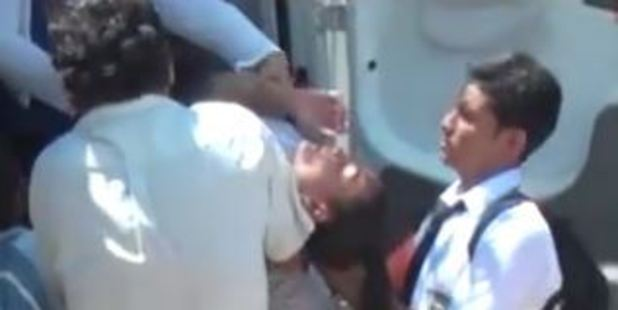 A schoolgirl being carried into an ambulance. Photo: VIA Televisión / YouTube
