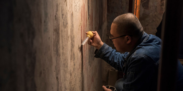 A technician working at the restoration of wall paintings in cave 98 of the Mogao grottoes. Photo / Gilles Sabrié for the Washington Post