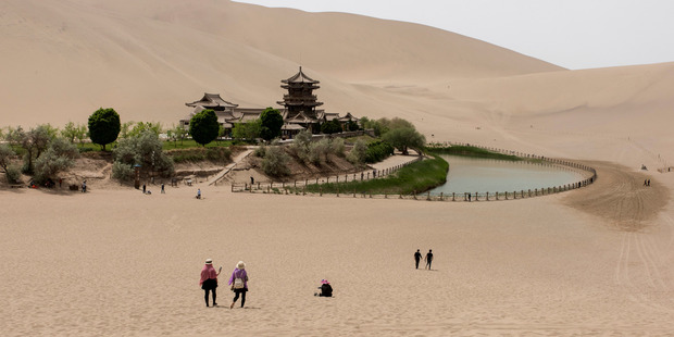 Tourists visit the Crescent Lake, one of Dunhuang's major tourist sites along with the Mogao caves. Photo / Gilles Sabrié for the Washington Post