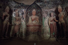 In a Mogao cave, lit by the flashlight of a guide, a Buddha statue surrounded by disciples dating from the Tang Dynasty. Photo / Gilles Sabrié For The Washington Post