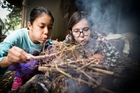 Adeline Wong and Estelle Hebley practise fire-lighting with flint in Michael Park School's outdoor classroom programme. Photo / Michael Craig