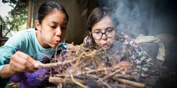 Loading Adeline Wong and Estelle Hebley practise fire-lighting with flint in Michael Park School's outdoor classroom programme. Photo / Michael Craig