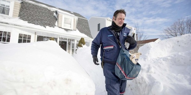 Postie John Bachman walks between high snow banks after delivering mail to a house in Hull, Massachusetts, in February. Photo / Bloomberg