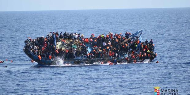 Italian Navy photograph show overloaded boat turning over as naval vessel approaches. Photo / AP