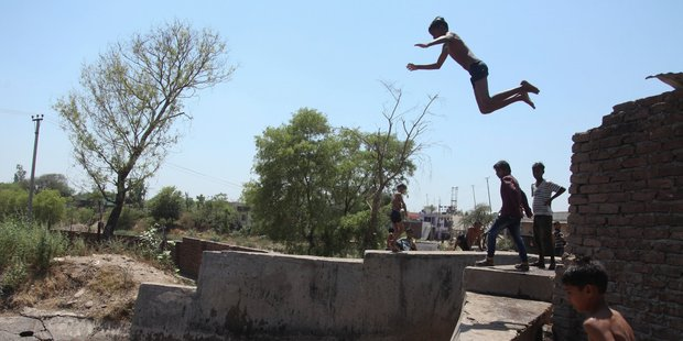 Children jump into a water canal to cool themselves on a hot summer day in Jammu. Photo / AP