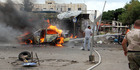 A firefighter, right, extinguishes a burning car at the scene where suicide bombers blew themselves up, in the coastal towns of Tartus, Syria, this week. Photo / AP