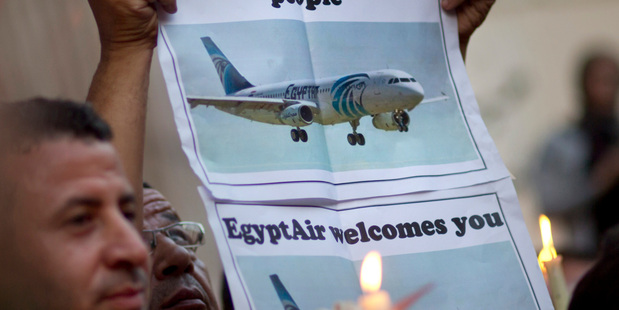 An Egyptian journalist holds a candle and a poster supporting EgyptAir during a candlelight vigil for the victims of MS804 in Cairo. Photo / AP