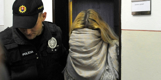 Maria Kukucova, right, hides her face in a scarf as she leaves a court after being taken into custody in Trencin, Slovakia, in 2014. Photo / AP