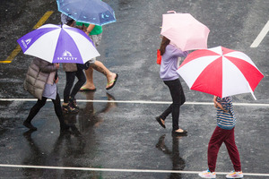 Pedestrians scurry across Queen Street in the heavy rain. Photo / Jason Oxenham