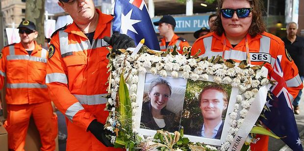 SES Volunteers carefully carry away a photo tribute of Katrina Dawson and Tori Johnson, the two victims of the Lindt Cafe seige. Photo / Getty