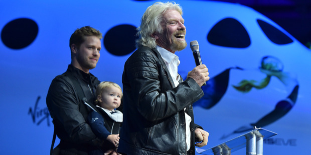 Richard Branson flanked by his son, Sam, and granddaughter, Eva-Deia Branson, 1, speaks to guests besides the WhiteKnightTwo launch vehicle in February. Photo / Getty Images