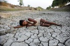 A child lies down on a dry bed of parched mud that is the dried up River Varuna at Phoolpur. Photo / AP