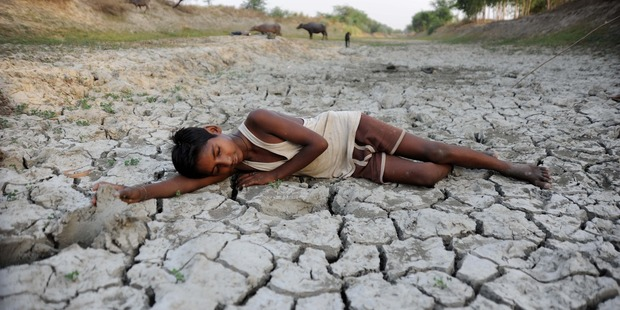 Loading A child lies down on a dry bed of parched mud that is the dried up River Varuna at Phoolpur. Photo / AP