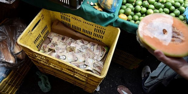 A vegetables container is used to put a large amount of bills of the sales of days in a local market in Caracas. Photo / Getty