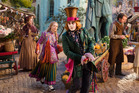Mia Wasikowska, in green skirt, plays an older Alice in the sequel also starring Johnny Depp, right, as the Mad Hatter. Photo / Supplied