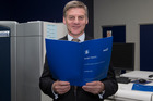 Finance Minister Bill English looking over a copy of his Budget 2016 speech during his visit to Printlink in Petone. Photo / Mark Mitchell