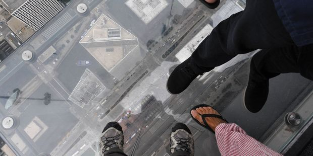 Feet on the glass balcony of the Willis Tower, Chicago.