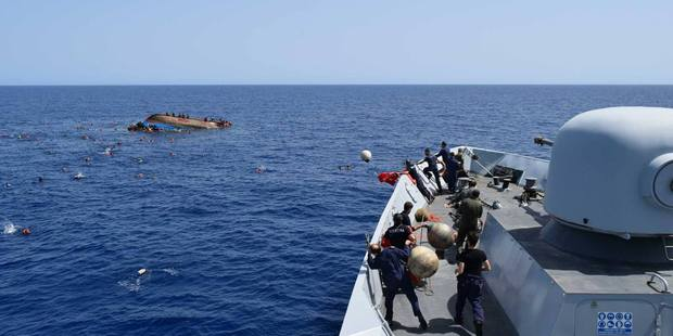 Italian Navy photograph show overloaded boat turning over as naval vessel approaches.Photo / Facebook