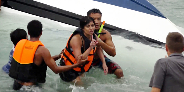 A woman gestures after she was rescued from a capsized boat on Koh Samui, Thailand. Photo / AP