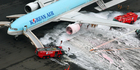 Firefighters gather near an engine of a Korean Air jet following an apparent engine fire on the tarmac at Haneda Airport in Tokyo. Photo / AP